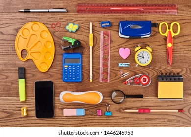 Different school supplies on wooden background. Desk with phone, alarm clock and various stationery items. Work and education concept. - Shutterstock ID 1446246953