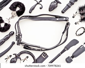 Different sex toys: dildo, vibrator, anal plug, clothespins on nipples, harness, prostate massager, bondage, handcuffs and others. There is an empty space in the center for the text