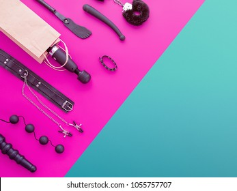 Different sex toys are on the background in the color-block style (fuchsia and green). The wand massager is in a paper shopping bag. The image is suitable for sex shop advertising