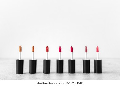 Different shades of lipstick applicators brush with Liquid lipstick makeup for lips on a grey background.