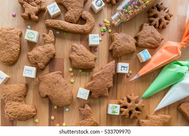 Different shapes of the christmas cookies prepared for decoration are on the wooden background. Colored icing closed to cookies.
