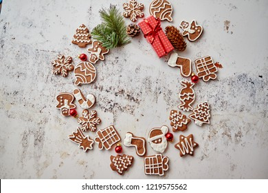 Different shapes of Christmas gingerbread cookies assorted in circle and placed od white rusty table. With copy space. Top view.