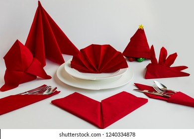 In different shapes folded luxury,red color  paper napkins on the white surface with elegance cutlery set and plate.Preparation for Christmas or New Year Feast.General view of napkins.