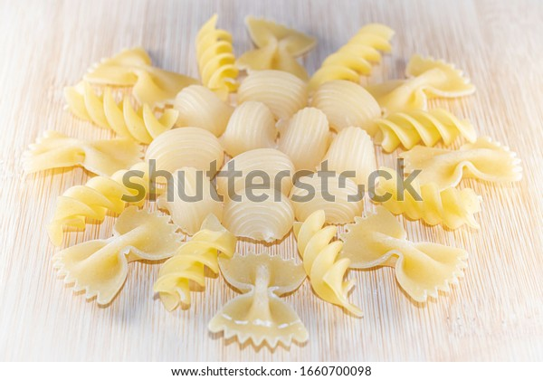 Different shapes of pasta collected in the form of a circle on a bamboo kitchen board