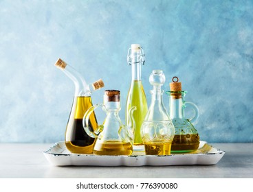 different shapes, types and sizes of cruets with olive oil on the table on a tray on blue