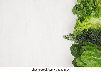 Different sheaves greens on white wooden background as decorative border, top view.