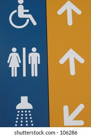 Different signs and arrows: wheelchair/disabled, toilets/WC, showers
