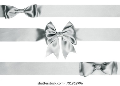 Different silver gift bow on the ribbon on white background