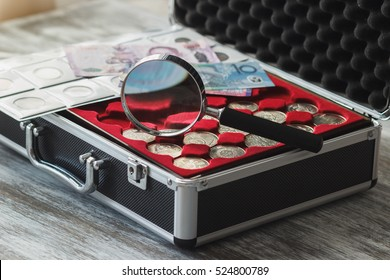 Different size collector's coins in the box and magnifying glass, soft focus background
