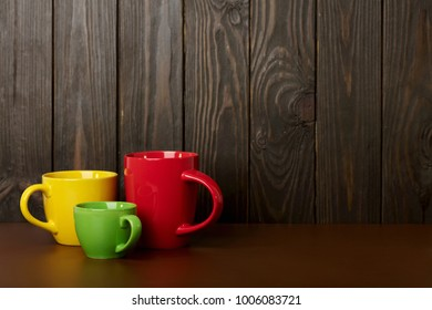 Different in size and color ceramic cups for coffee and tea - red, yellow and green on a dark wooden background. Selective focus.