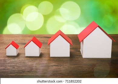 Different Size Of House Models In Row On Wooden Desk