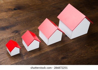 Different Size Houses In Row On Wooden Table