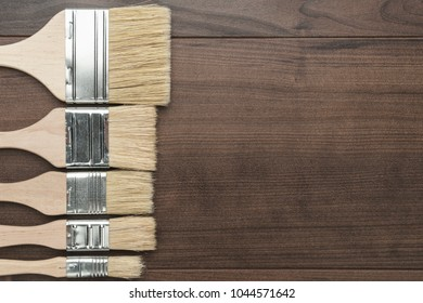 different size paint brushes on the brown wooden table