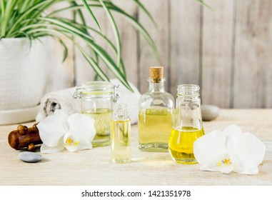 Different size and shape transparent glass jars and bottles with massage and essential oils on table, natural wooden background, white orchid and candles for decoration. Beauty spa background concept.