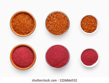 Different sized bowls with chili pepper and sumac spices, isolated on white background, top view