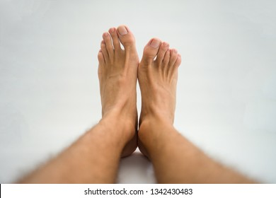 Different sized feet, one foot bigger the the other, white background