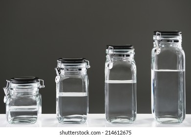 Different sized jars lined up from smallest to biggest with water on gray background