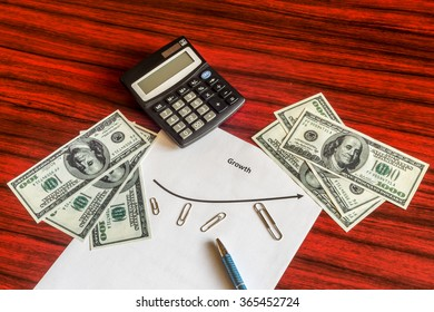Different sized Paper clips arranged around a curve graph symbolising business growth. Calculator, 100 dollar bills and a pen lying aside.