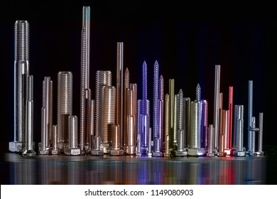 Different sizes of screws on black background,