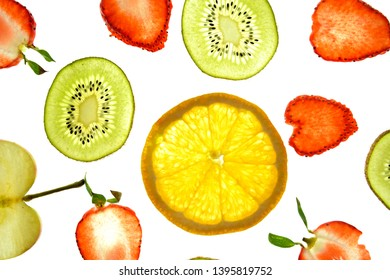 Different sliced fruits like orange, strawberries and kiwi lies on a bright white background and are illuminated from above with light - concept with fresh and healthy fruits in different colors