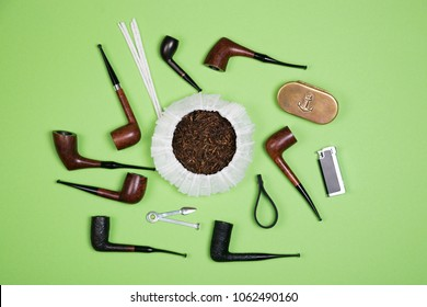 Different smoking tobacco pipes and pipe smoking accessories on green background. Top view.