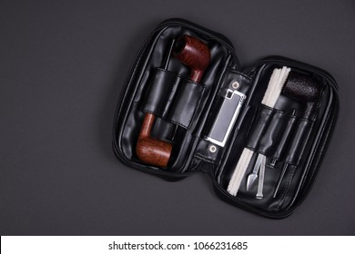 Different smoking tobacco pipes, tobacco tamper and lighter in a black leather bag on dark background with copy space.