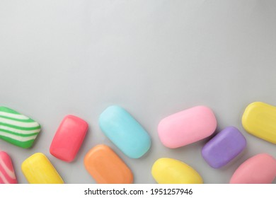 Different soaps in different soap dishes. A lot of solid soap for hygiene and cleanliness. Colorful soap and remnants are scattered on grey background. Top view.