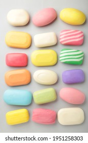 Different soaps in different soap dishes. A lot of solid soap for hygiene and cleanliness. Colorful soap and remnants are scattered on grey background. Vertical foto