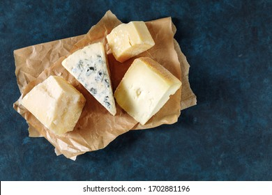 Different sorts of cheese on a parchment paper on dark blue textured background. Top view