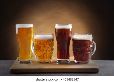 Different sorts of draft beer in glasses on wooden table