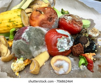 Different sorts of rotten fruits and vegetables on gray paper