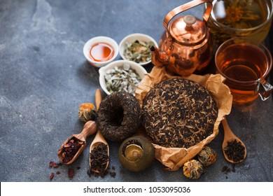 Different sorts of tea; Asian pressed pu-erh tea, shu pu'er in tangerine, blooming tea in ball, hibiscus, herbal on dark slate background