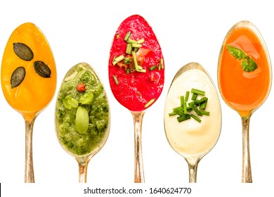 Different soups in orange green white red on a spoon