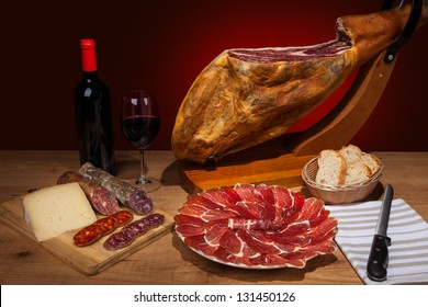 Different spanish embutidos on a table: jamon, chorizo, salami, cheese and a bottle of wine