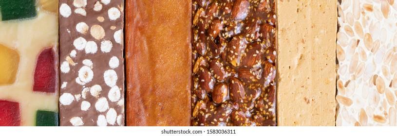 Different Spanish turron or nougat, hard almond, soft almond, chocolate, burnt egg yolk guirlache, glace fruit nougat. Spanish Christmas sweet large background.