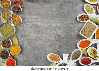 Different spices in bowls and spoons on grey background