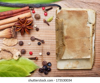 Different spices, herbs and old recipe book on wooden background