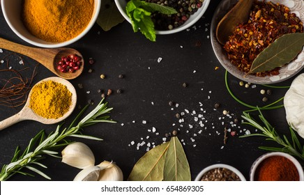 Different spices and herbs on a black stone - Shutterstock ID 654869305