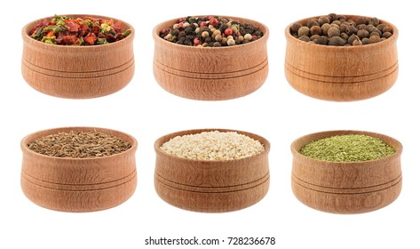 Different spices and herbs in wooden pots isolated on white background