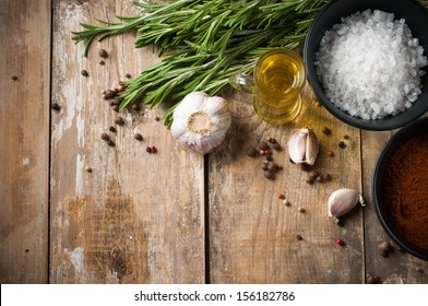 Different spices, rosemary, allspice, garlic, oil and salt on a wooden board, rustic kitchen background