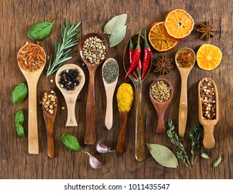 Different spices in wooden spoons on wooden background. Top view. Mock-up.