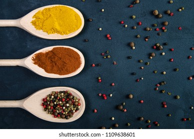 Different spices in wooden spoons and pepper scattered on concrete background