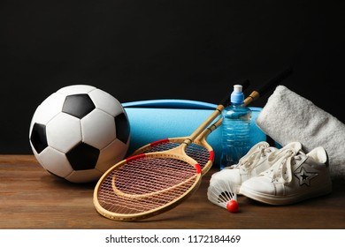 Different sports equipment on wooden table on black background. Concept sport.