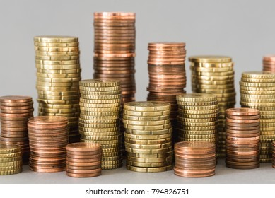 Different stacks of euro coins in front of grey background symbolizing savings