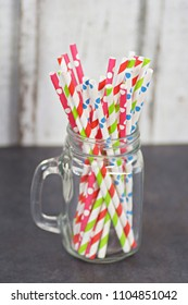 Different straws in a glass in front of a wooden background