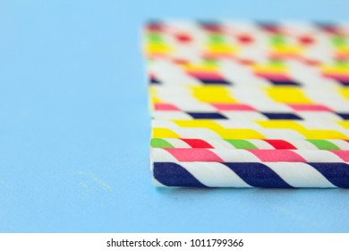 different straws for juice on a blue background
