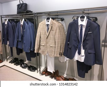 Different suits with shirts, and leather shoes in shop
