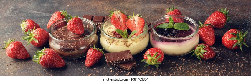 Different summer cheesecakes in jars on a brown background