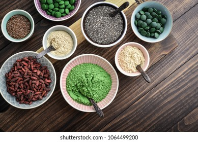 Different super foods in bowls on a wooden background, top view