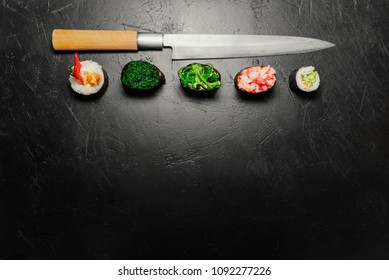 Different Sushi with Japanese knife on black stone slate background. Sushi on a table. Space for text. Top view. Sushi background. food frame
